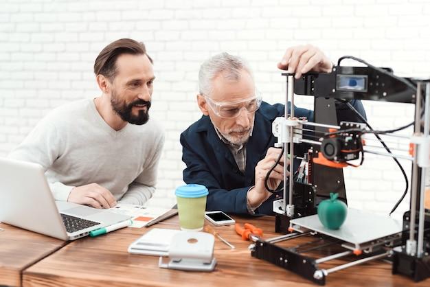 Deux ingénieurs impriment les détails sur l'imprimante 3d.