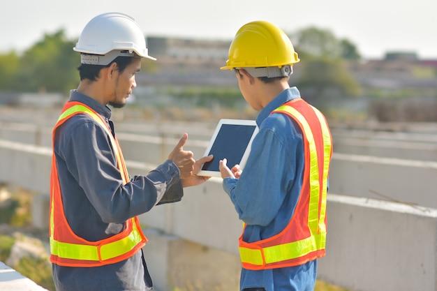 Deux ingénieurs parlent communication utilisent l'inspection de la tablette au chantier de construction