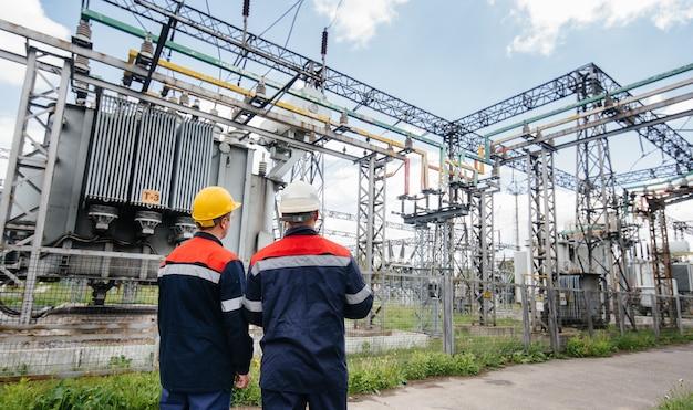 Deux ingénieurs spécialistes des postes électriques inspectent les équipements modernes à haute tension. énergie. industrie.