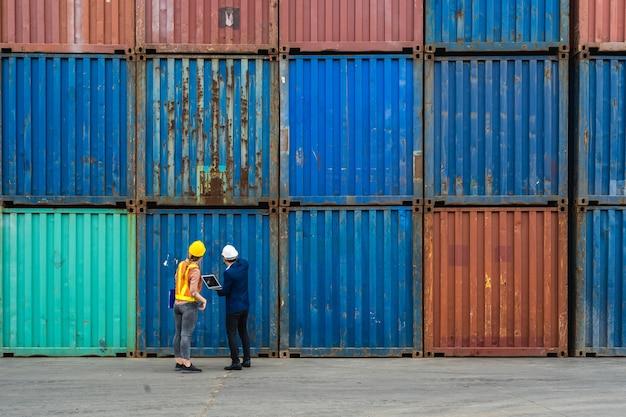 Deux ingénieurs tiennent un ordinateur portable, un document pour vérifier la qualité de la boîte de conteneurs d'un cargo pour l'exportation et l'importation, fond de conteneur bleu