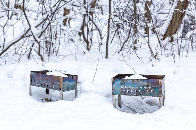 Deux installations de barbecue ou brasero oubliés dans la forêt d'hiver sur la neige