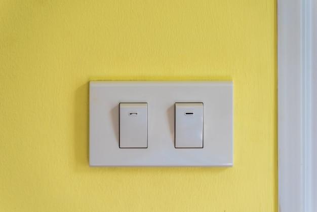 Deux interrupteurs d'éclairage blancs sur un mur de béton jaune