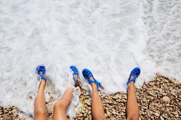 Deux jambes de filles kid dans un rivage de mousse de plage