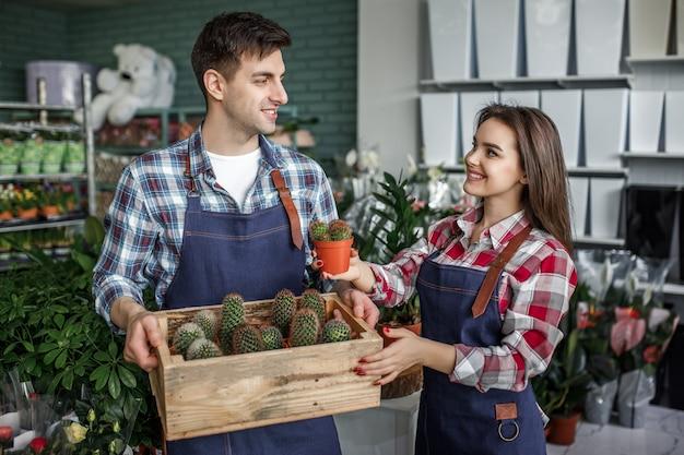 Deux jardiniers souriants heureux tenant un pot avec un petit cactus dans un magasin de fleurs