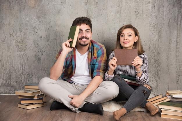 Deux, jeune couple, poser, à, tas livres