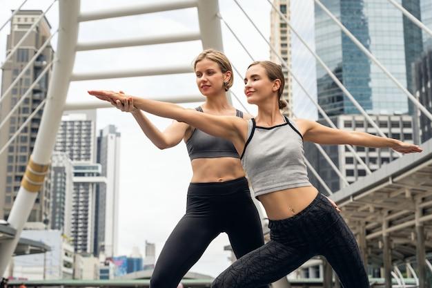 Deux de jeune femme debout dans la ville pratiquant le yoga dans la posture du guerrier