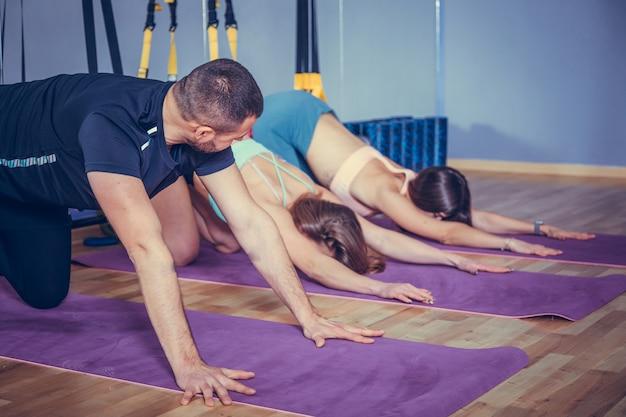 Deux jeune femme en forme de faire des exercices dans la salle de gym avec leur entraîneur de fitness.