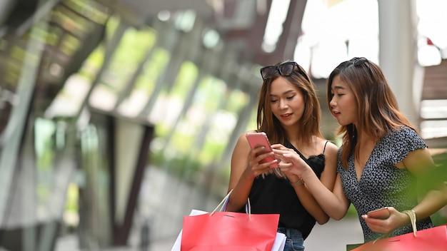 Deux jeune femme regardant smartphone avec concept de magasinage.