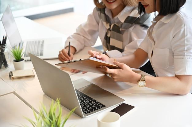 Deux jeune femme rencontre avec le projet d'entreprise de démarrage sur la table de travail.