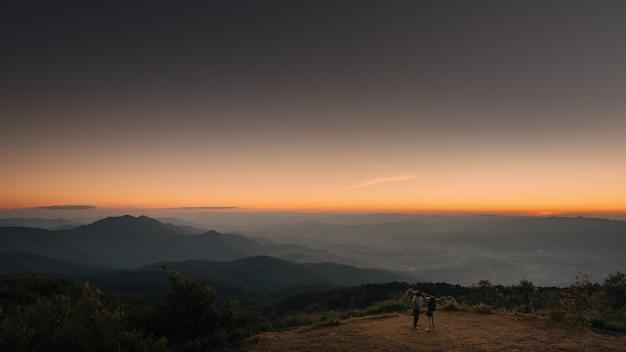 Deux Jeune Homme Debout Sur Le Coucher De Soleil Et Profiter De La Vue De La Nature Avec Twlight. Photo Premium