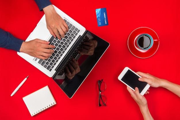 Deux jeune homme utilisant un ordinateur portable et un smartphone.focus sur la main