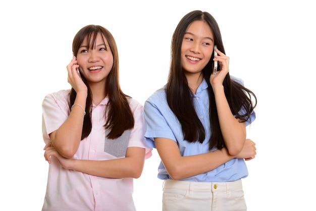Deux jeunes adolescentes asiatiques heureux souriant et parlant sur mobil