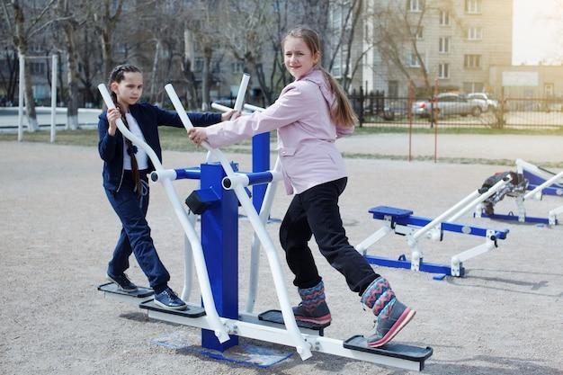 Deux jeunes adolescentes en costume de sport, aux cheveux longs souriants et faisant des exercices dans la rue sur les simulateurs. sport, fitness, concept d'entraînement de rue.