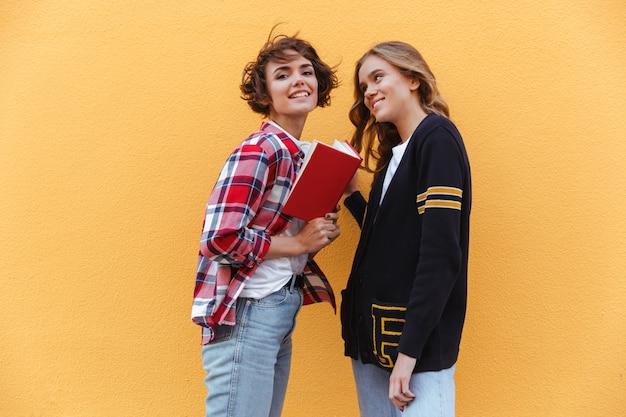 Deux jeunes adolescentes avec des livres à l'extérieur