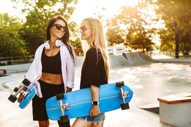 Deux jeunes adolescentes séduisantes tenant des longboards en se tenant debout au skatepark