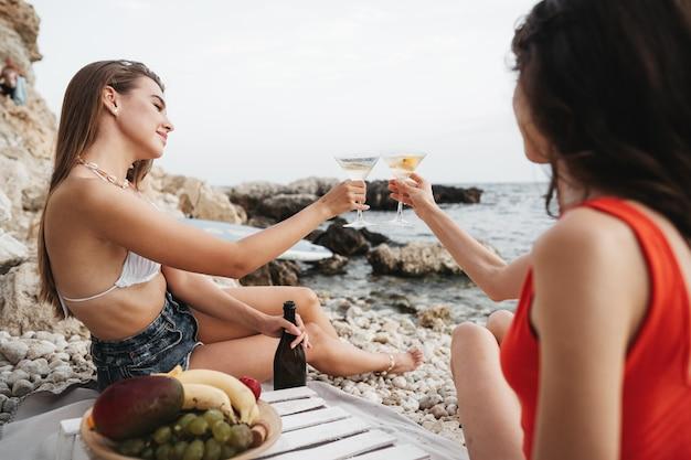 Deux jeunes amies ayant un pique-nique sur une plage buvant des cocktails
