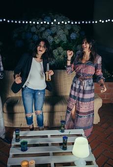 Deux jeunes amies heureuses dansant et s'amusant dans une fête en plein air. concept d'amitié et de célébrations.