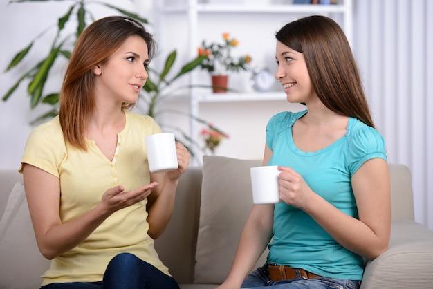 Deux jeunes amies heureux avec des tasses à café.