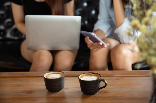 Deux jeunes amies avec le smartphone sur la main parler et boire assis sur un canapé dans le café café.
