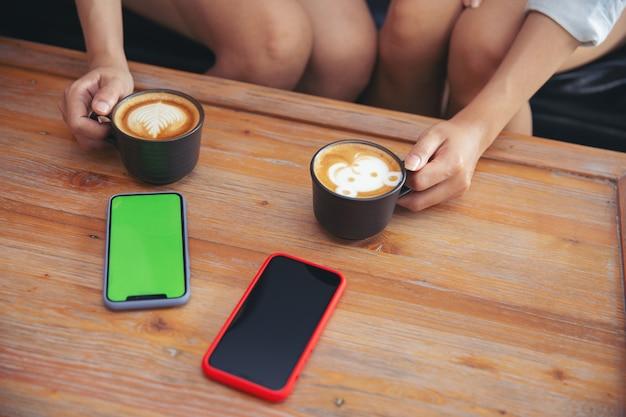 Deux jeunes amies avec smartphone parlant et buvant assis sur un canapé dans le café.