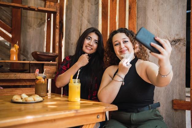 Deux jeunes amis adorables et heureux prennent un selfie dans un bar.