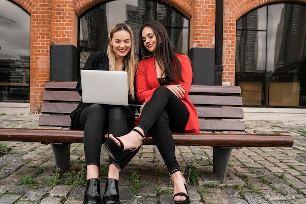 Deux jeunes amis à l'aide d'un ordinateur portable à l'extérieur.