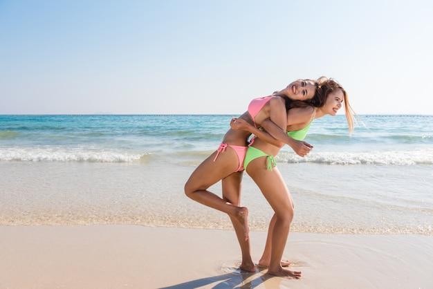 Deux jeunes amis asiatiques et brunes qui regardent la caméra et vous envoient un bisou à l'air, ont un corps sexy et mince, des lunettes de soleil en bikini et des bijoux brillants à la mode, posant devant une plage tropicale.