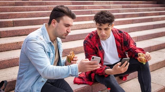 Deux jeunes amis assis dans les escaliers dans un parc et mangeant