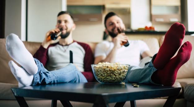 Deux jeunes amis barbus heureux regardant la télévision ou un match de sport assis sur le canapé à la maison le week-end et buvant des bières et mangeant des collations