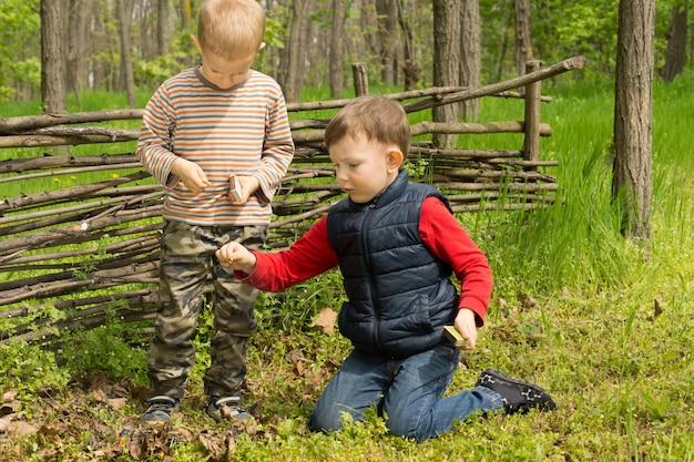 Deux jeunes amis jouant dans un bâtiment boisé et allumant un petit feu de camp