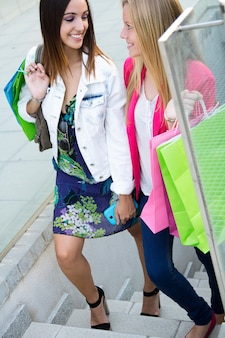 Deux jeunes amis sur les marches du parking en après-midi shopping