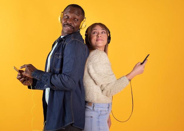 Deux jeunes amis souriants isolés avec. concept de mode de vie des personnes. écoutez de la musique avec des écouteurs tenant un téléphone mobile avec un écran vide vide montrant le pouce vers le haut