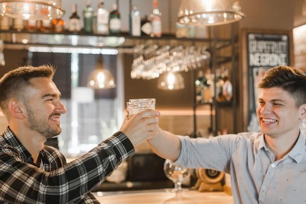 Deux jeunes amis souriants soulevant des toasts au bar