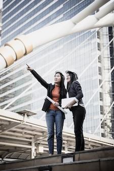 Deux jeunes architectes regardant plan directeur devant le chantier de construction.