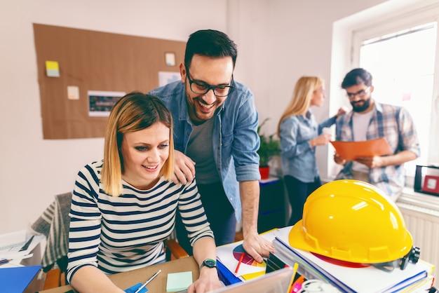 Deux jeunes architectes souriants travaillant sur un grand projet
