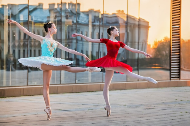 Deux jeunes ballerines dans un tutu rouge et bleu vif dansent sur fond de reflet du coucher de soleil de la ville