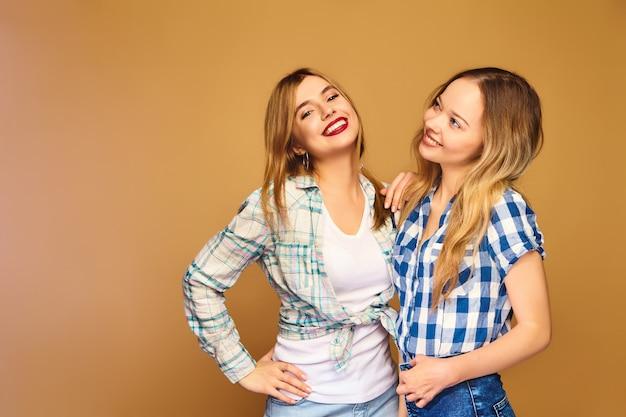 Deux jeunes belles blondes souriantes en chemises à carreaux d'été à la mode