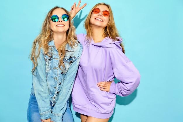 Deux jeunes belles blondes souriantes hipster femmes dans des vêtements d'été à la mode. femmes sexy sans soucis posant près du mur bleu à lunettes de soleil. des modèles positifs qui deviennent fous