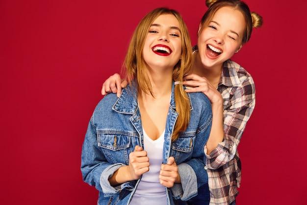 Deux jeunes belles blondes souriantes hipster femmes posant dans des vêtements à la mode chemise à carreaux d'été