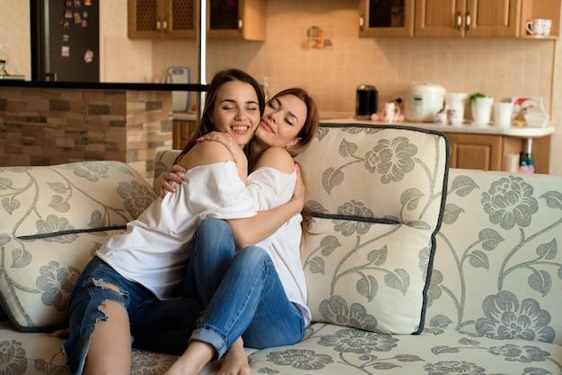 Deux jeunes belles copines joyeuses en blue-jeans assis sur un canapé à la maison en riant.