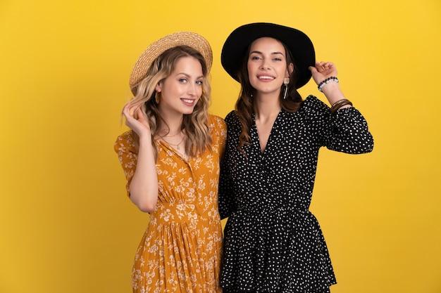 Deux jeunes belles femmes amies ensemble isolées sur jaune en robe noire et jaune et chapeau tendance boho élégant