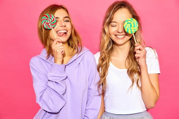 Deux jeunes belles femmes blondes blondes souriantes dans des vêtements d'été à la mode. femmes chaudes insouciantes posant près du mur rose. les modèles positifs couvrent les yeux par sucette