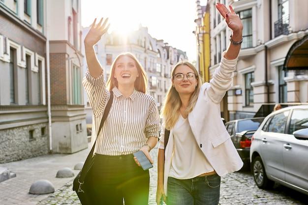 Deux jeunes belles femmes heureuses étudiantes à l'université marchant le long de la rue de la ville, des femmes souriantes riant regardant vers l'avant en agitant la main