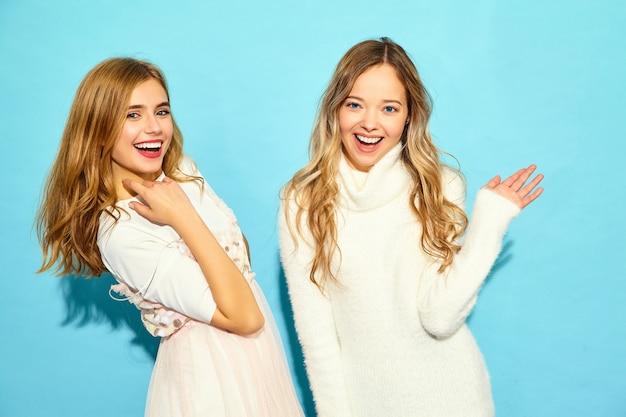 Deux jeunes belles femmes hipster souriantes dans des vêtements d'été blancs à la mode. femmes insouciantes sexy posant près du mur bleu. modèles positifs