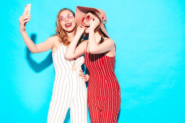 Deux jeunes belles femmes hipster souriantes dans des vêtements de salopette d'été à la mode