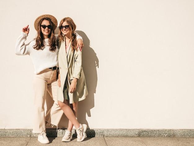 Deux jeunes belles femmes hipster souriantes en pull et manteau blancs à la mode