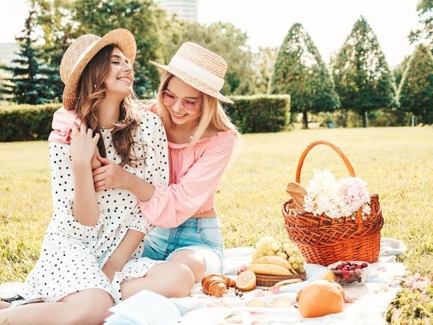 Deux jeunes belles femmes souriantes en robe d'été à la mode et chapeaux. femmes insouciantes faisant un pique-nique à l'extérieur.