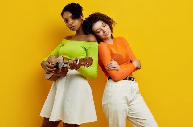 Deux jeunes belles femmes en vêtements d'été colorés avec petite guitare