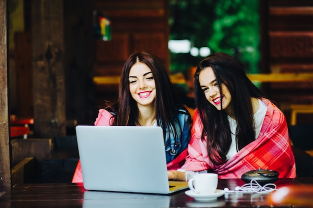 Deux jeunes et belles filles assises à la table et cherchant quelque chose sur internet