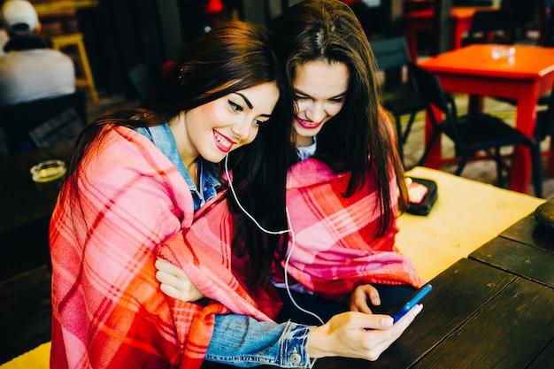 Deux jeunes et belles filles assises à la table écoutant de la musique avec un smartphone